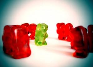 Bild von einem grünen Gummibärchen in der Mitte und vielen roten herum